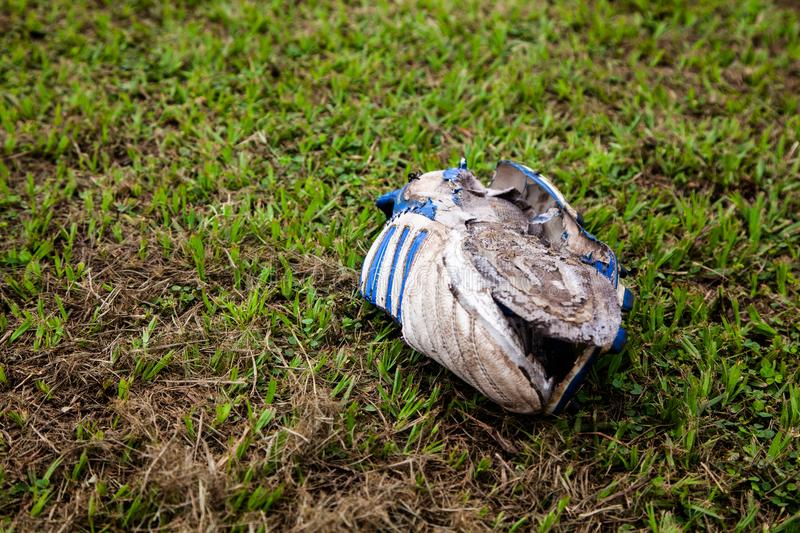 Old football boot rots on grass stock photos