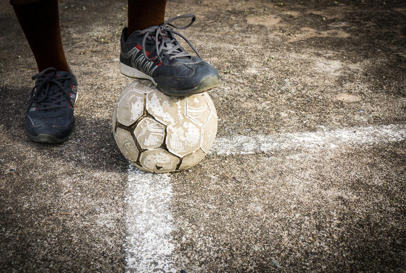 Old Football On Concrete Field. With Soccer Boots stock image