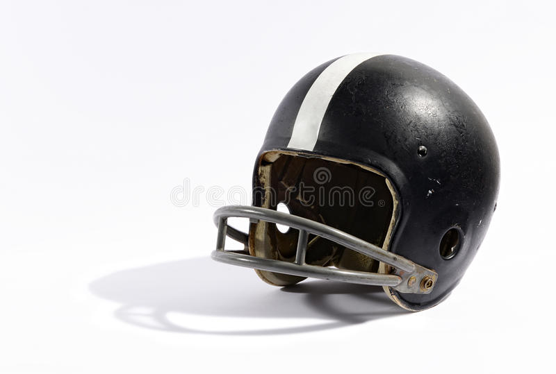 Old football helmet. Old black football helmet with a metal face protection guard and white decorative stripe on a white background stock photos