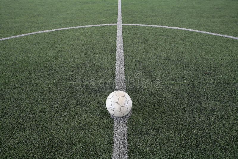 Old football at kick off mark on fake grass. Field royalty free stock photo