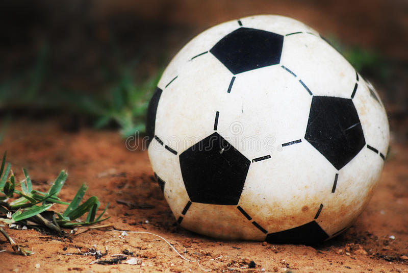 Old football. A picture of an old and flat football laying on the ground stock images