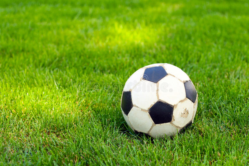 Old football, soccer ball on the grass. Selective focus royalty free stock image