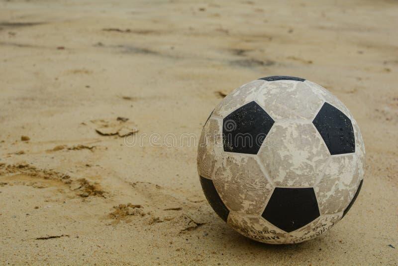 An old football or soccer ball on sand stock photography
