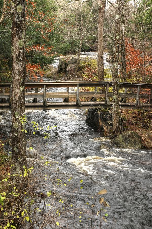 Old footbridge over a stream in small upstate New York town. In the Fall royalty free stock photography