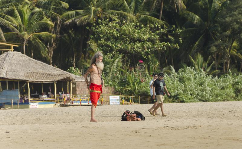 An old foreign tourist standing in yogi attire on the sand beach royalty free stock photo