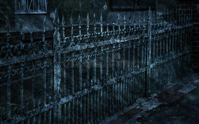 Old forged iron cast iron fence with sharp spears and cracked paint from time to time. White dirty abandoned fence that broke royalty free stock photography