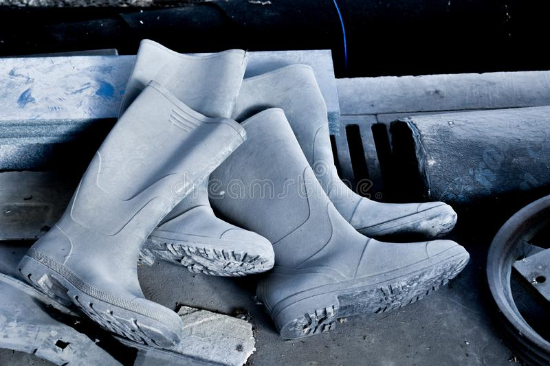 Old forgotten working rubber boots, discarded on the floor. Factory dirty floor stock photography