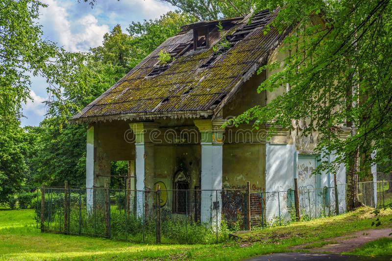 Vintage forlorn house deep in city park with lush green foliage. Old forlorn abandoned house deep in a city park with lush green foliage royalty free stock photos