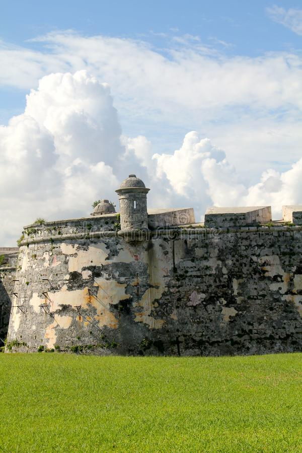 Old fort wall in Havana, Cuba. Old fort wall with look out, under cloudy blue sky with grass in front royalty free stock photography