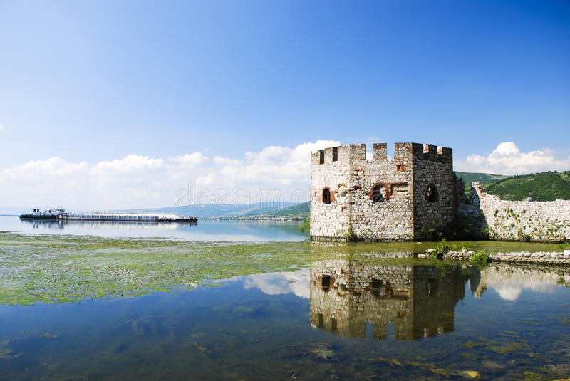 Old fortress and barge on river stock photo