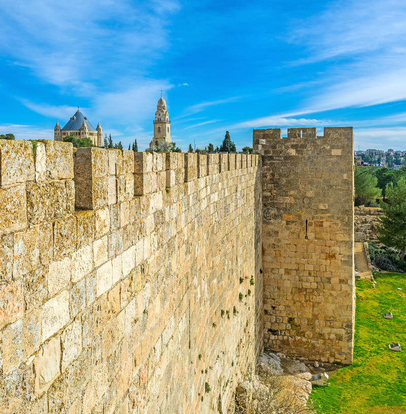 The old fortress. The old city wall is neighboring with the Bonei Yerushalayim garden and hides the massive building of Dormition Abbey with the high belfry on stock image