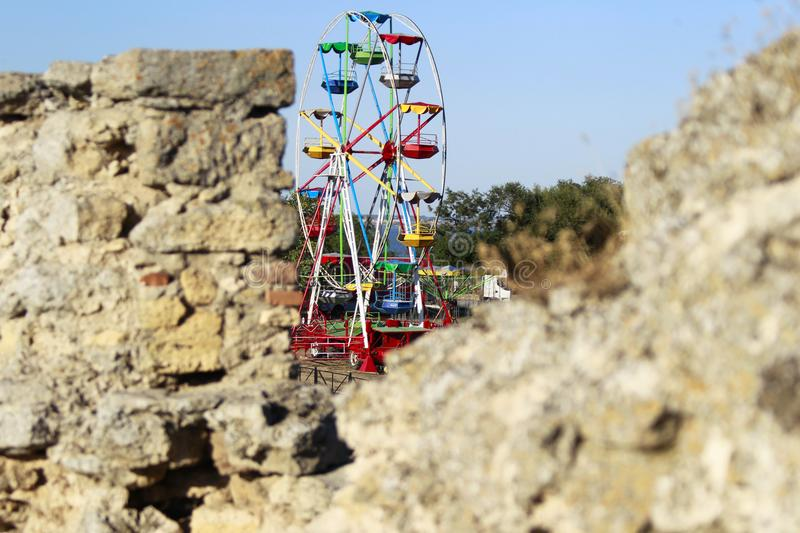 History and modernity. An old fortress and a modern roundabout. History and modernity. Ancient bricks and a Ferris wheel stock photos