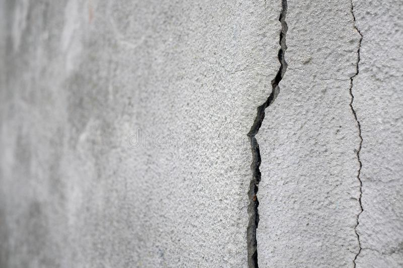 Old foundation and plaster wall with cracks. Building requiring repair closeup stock photo