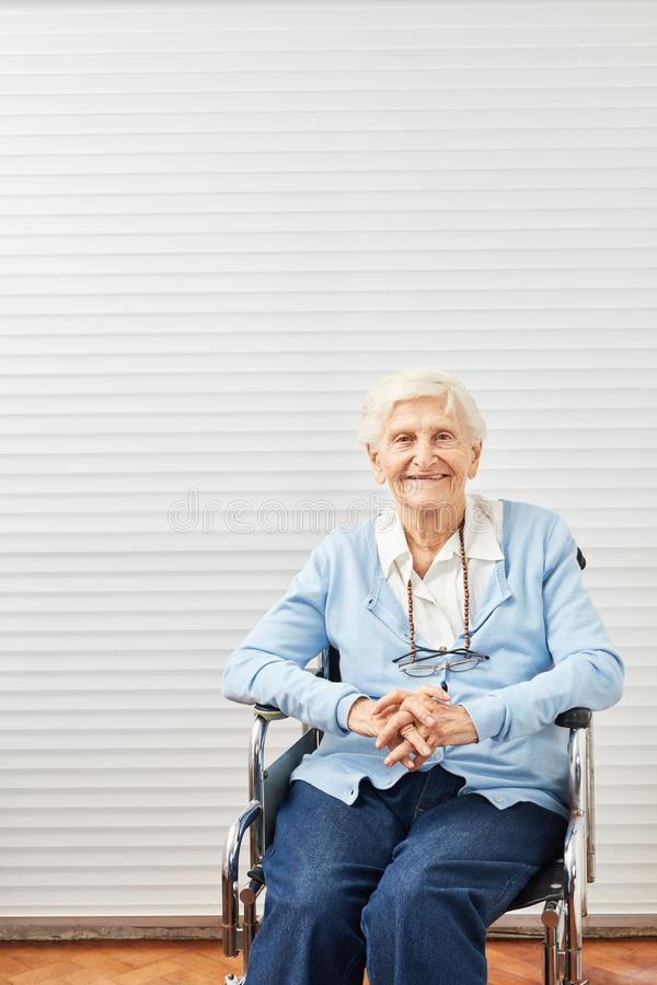 Old senior woman is sitting smiling in wheelchair stock photography