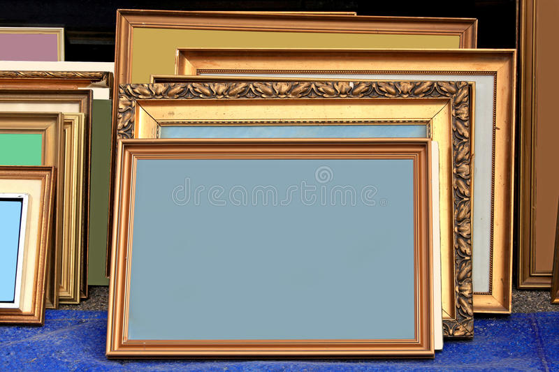 Old frames. Many old gold frames stacked next to wall stock photos