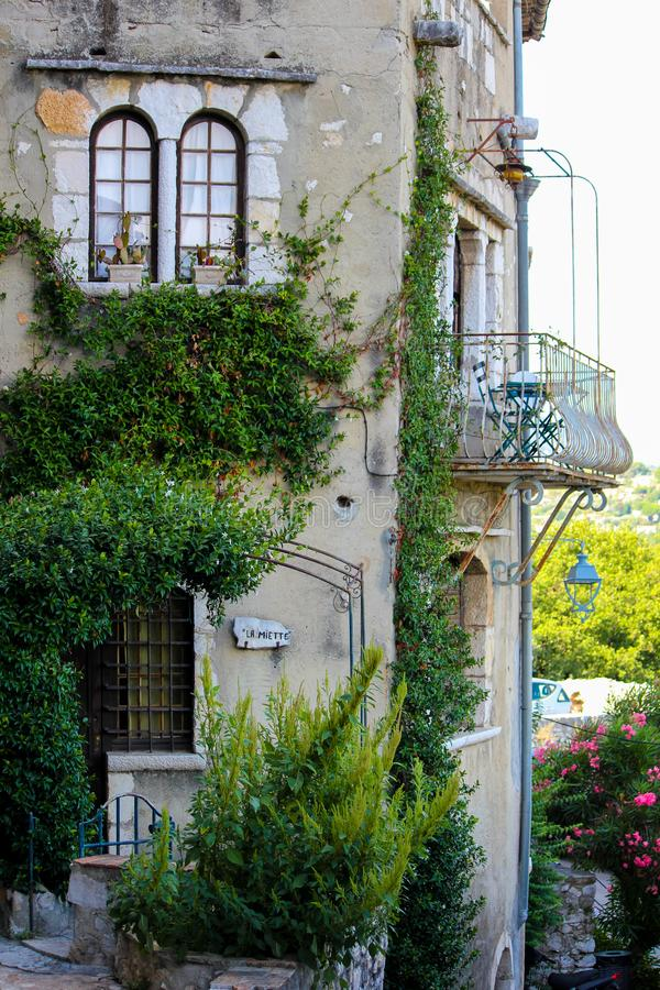 Old French house with a climbing plant and a wrought-iron balcony in Mougins in Provence royalty free stock photo