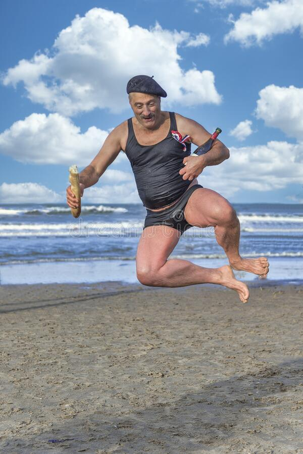 Old French man jump on the beach. Old hated French man jumping and dancing on the beach holding the traditional French food in hands which are the red wine and
