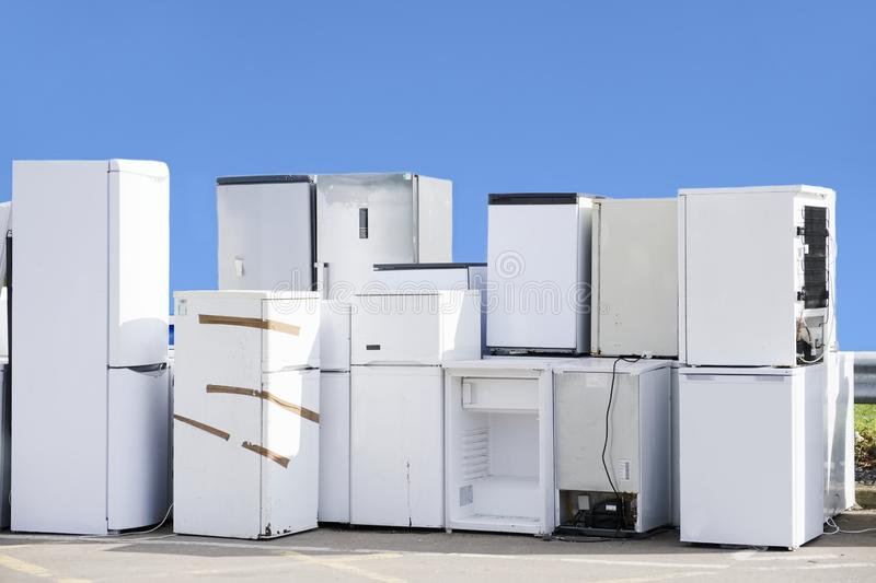 Old fridges freezers refrigerant gas at refuse dump skip recycle stacked pile help environment reduce pollution white silver blue. Sky uk stock photo