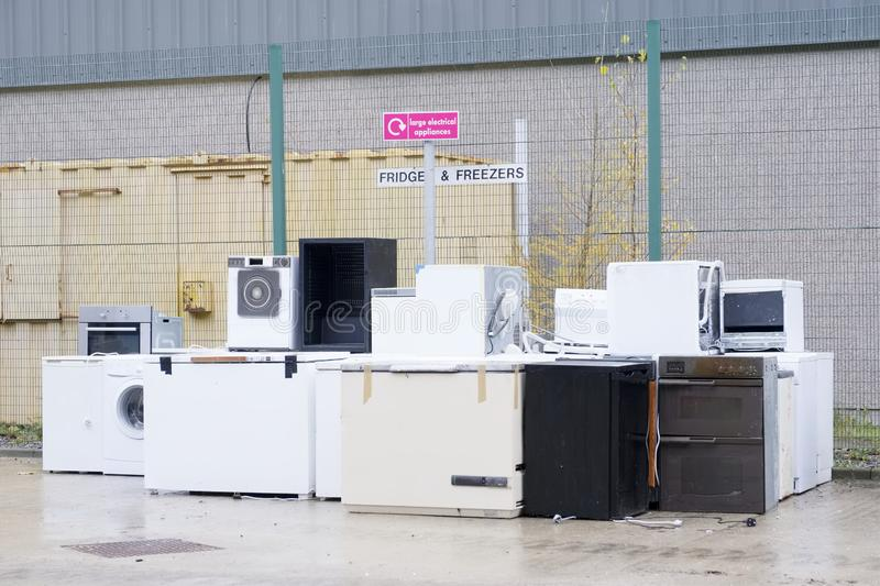 Old fridges freezers refrigerant gas at refuse dump skip recycle stacked pile plant help environment reduce pollution white silver. Uk royalty free stock photography