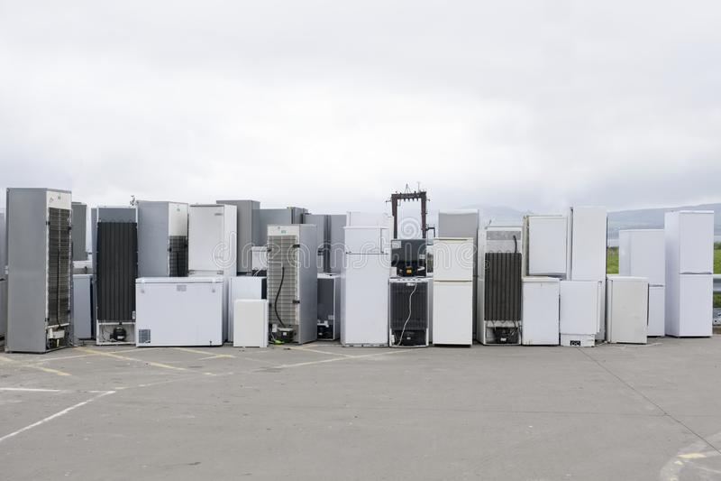 Old fridges freezers refrigerant gas at refuse dump skip recycle stacked pile plant help environment reduce pollution white silver. Uk stock image