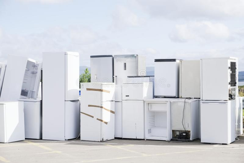Old fridges freezers refrigerant gas at refuse dump skip recycle stacked pile plant help environment reduce pollution white silver. Uk royalty free stock photo