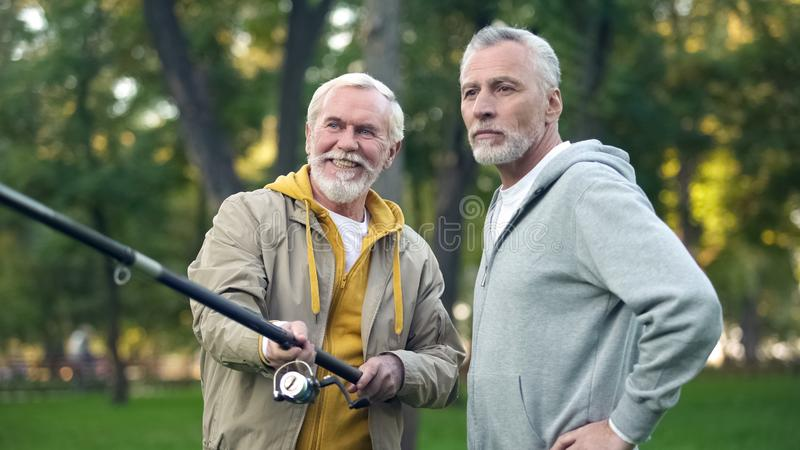 Old friends catching spinning fish, retirement hobby, weekend activity outdoor stock photography