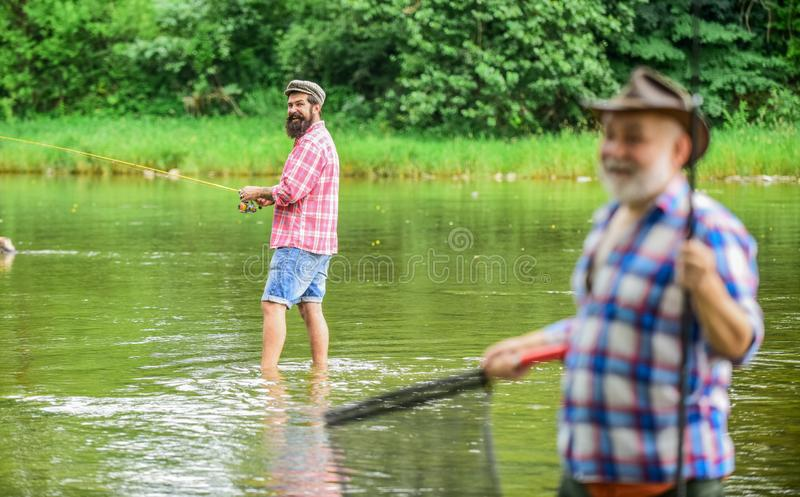 Old friends. family bonding. summer weekend. two fishermen with fishing rods, selective focus. mature man fisher. hobby stock photos