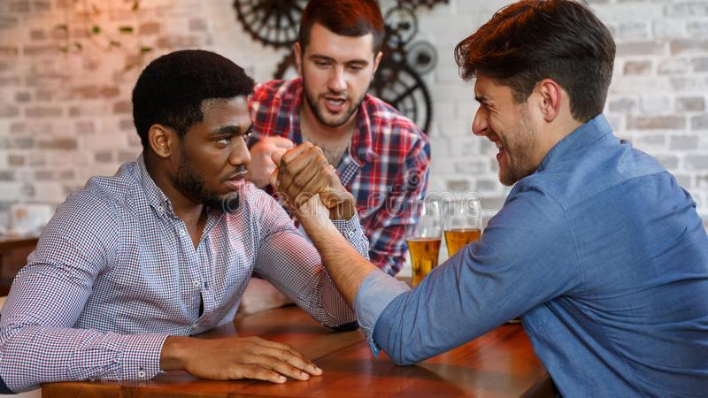 Old friends having arm wrestling challenge in a pub. Old friends having arm wrestling challenge, meeting in a pub royalty free stock photo