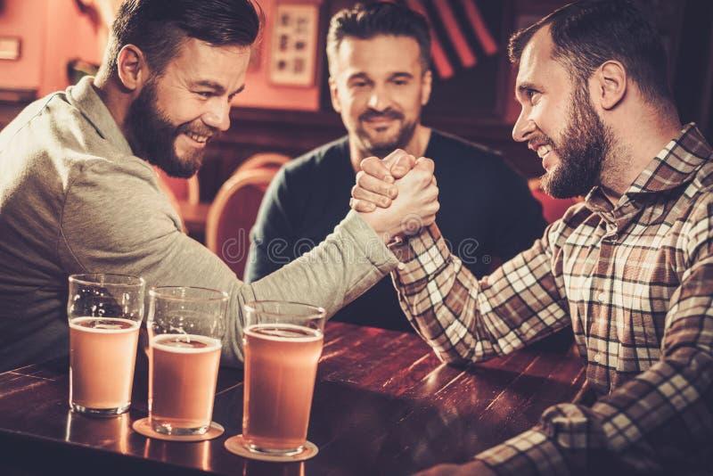 Old friends having fun arm wrestling each other in pub. Cheerful old friends having fun arm wrestling each other in pub stock photography