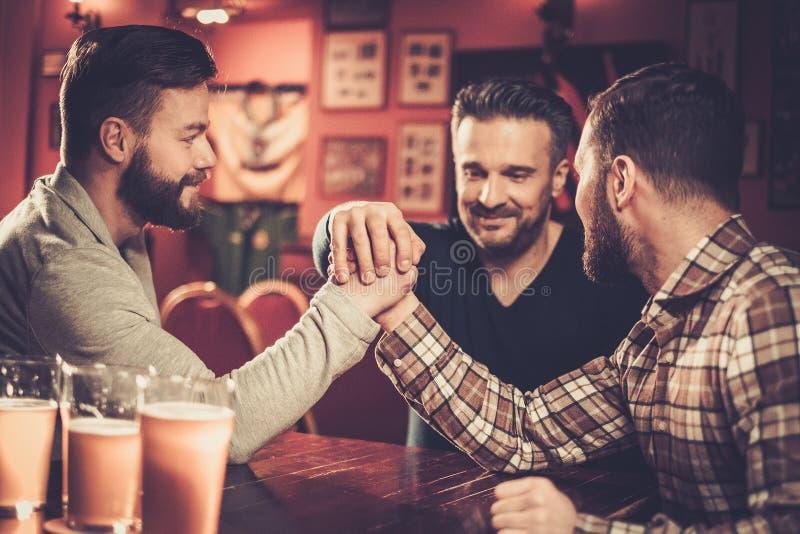 Old friends having fun arm wrestling each other in pub. Cheerful old friends having fun arm wrestling each other in pub royalty free stock photos
