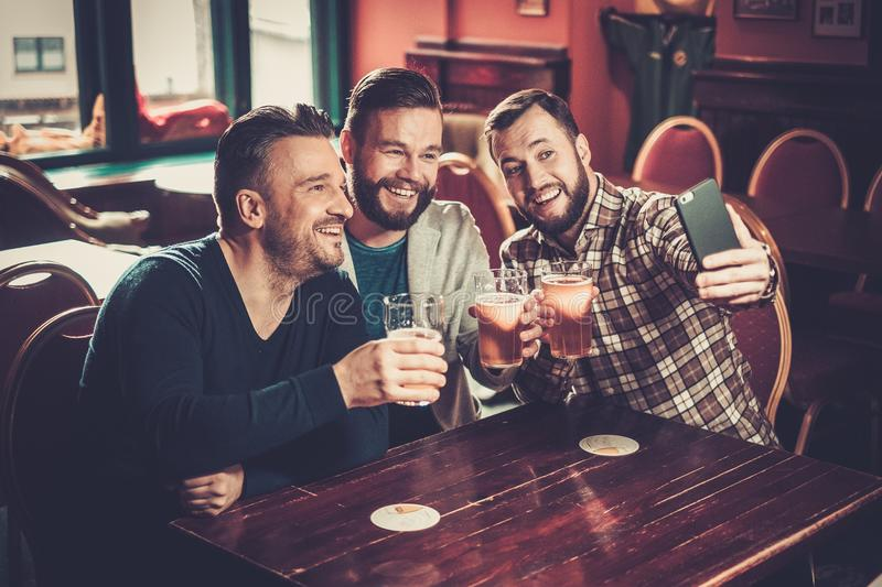 Old friends having fun taking selfie and drinking draft beer in pub. Cheerful old friends having fun taking selfie and drinking draft beer in pub royalty free stock photography