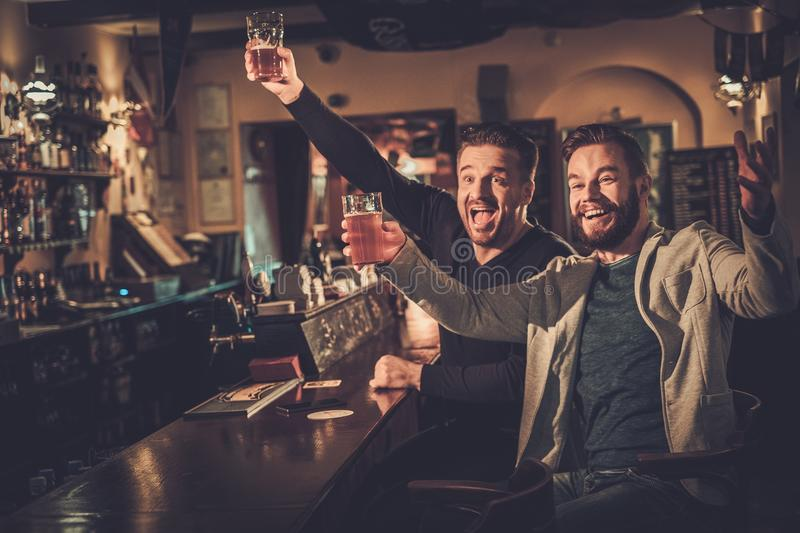 Old friends having fun watching a football game on TV and drinking draft beer at bar counter in pub. Cheerful old friends having fun watching a football game on royalty free stock images