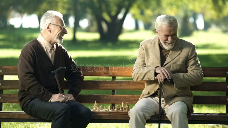 Old friends sitting on bench in park and remembering young years, playing chess stock image