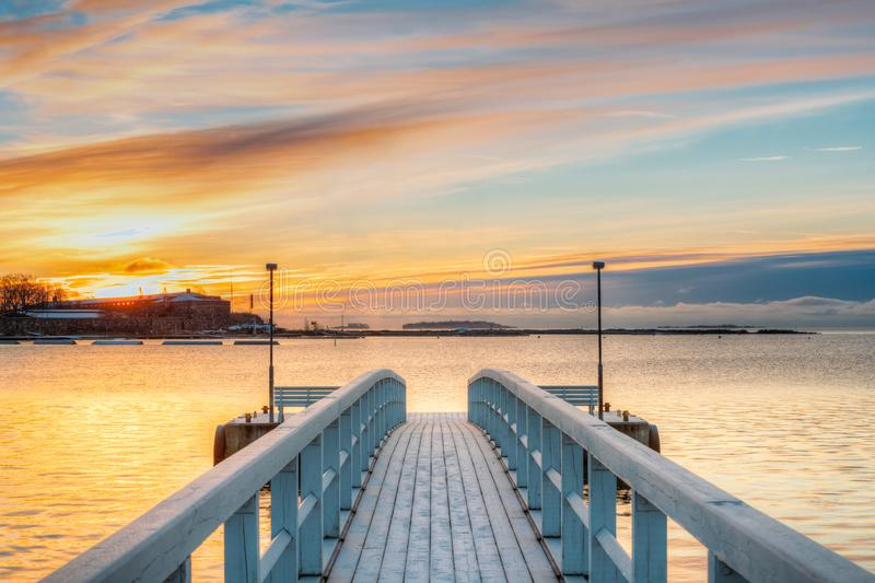 Old Frosted Wooden Boards Pier On Calm Water Of Lake Or River Or Sea At Evening Or Morning Time. Sunset Sunrise In stock photos
