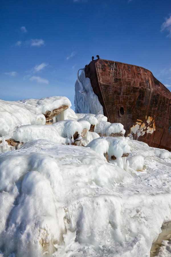Old frozen ship on the bank of Olkhon island on siberian lake. Old frozen castaway ship on the bank of Olkhon island on siberian lake Baikal at winter time royalty free stock images