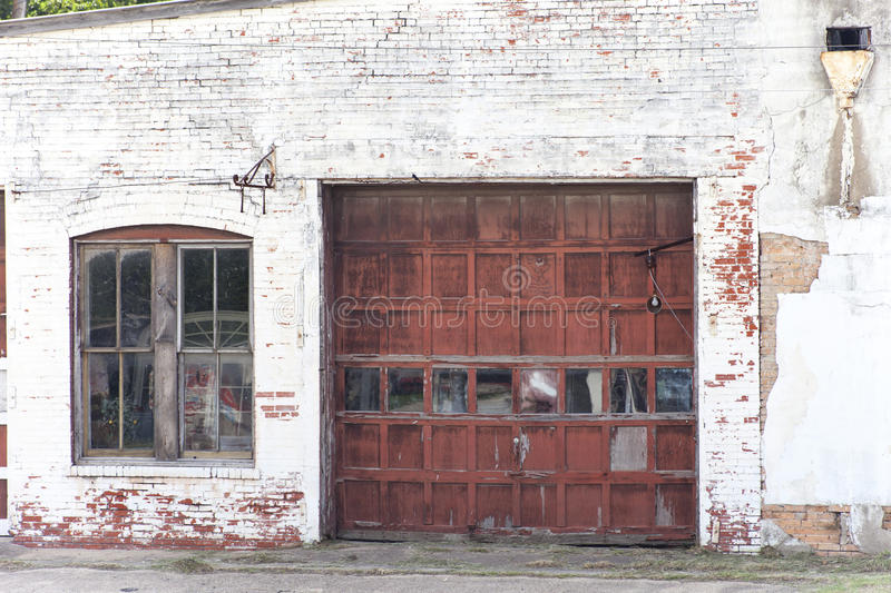 Old Garage. An old brick garage with red door and stock photo