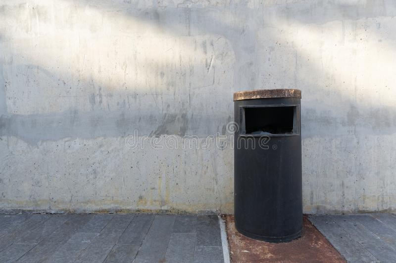 Old garbage bin of steel on wooden floor with concrete background royalty free stock photos