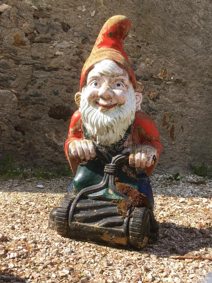Old Garden Gnome. An image of a unique antique garden gnome with a push lawn mower stock images