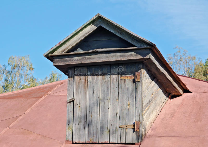 Old garret door. On vintage roof top stock image