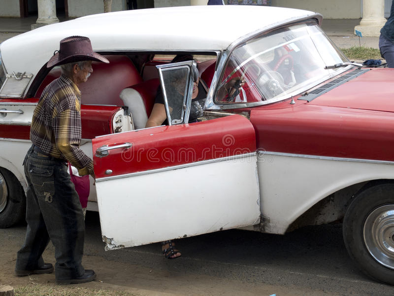 Old gaucho opening a door of a vintage car. stock images