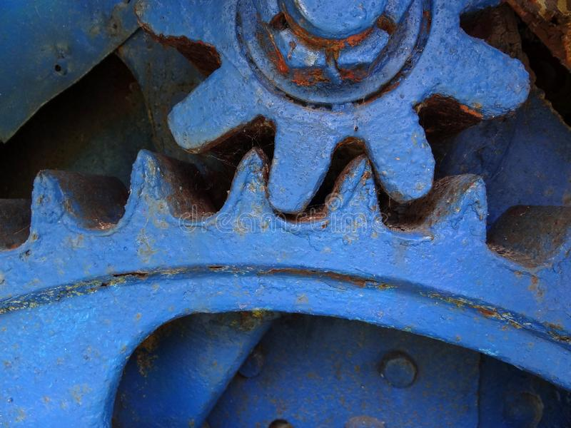 Old gear wheels. Close up mechanical parts. Blue painted gear wheels detail. Symbol for teamwork and cooperation stock images