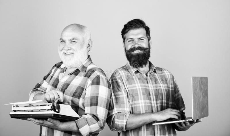 Old generation. bearded men. Vintage typewriter. father and son. family generation. retro typewriter vs laptop. New royalty free stock photography