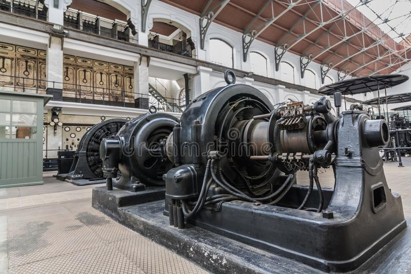 Old generator on powerhouse. bottom view on big black iron electric installation with flywheel and cables in power plant. Old generator on powerhouse royalty free stock image