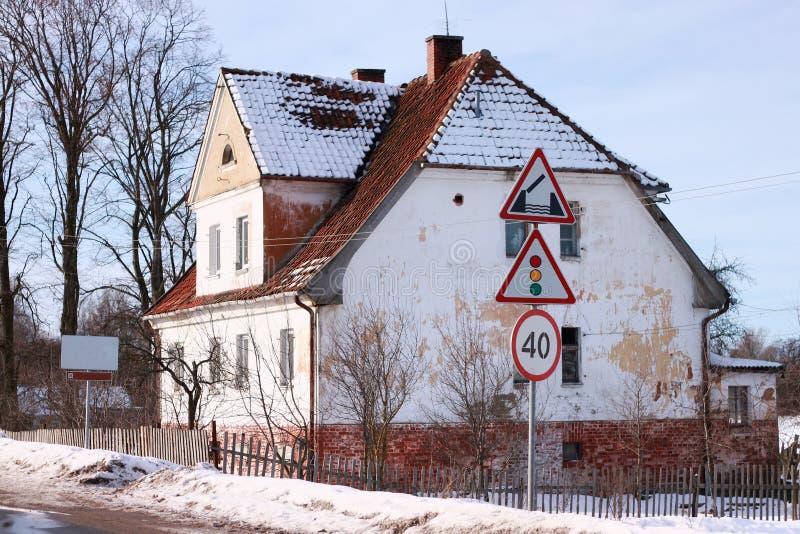 Old german building near road signs. In Polessk Labiau. Kaliningrad region, Russia stock photos
