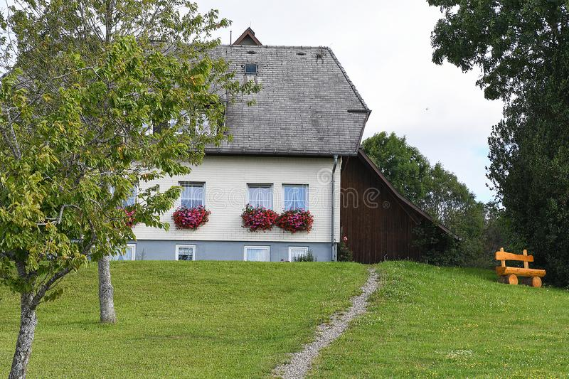 Old German house with flower box. Old house with flowers in window box and wooden log bench in Black Forest Germany royalty free stock image