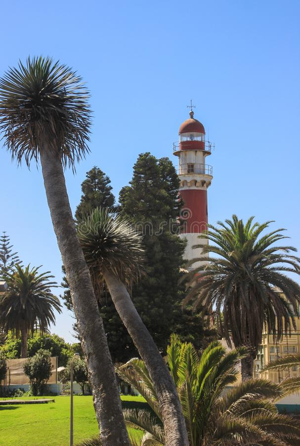 Old German red and white lighthouse, which is called `bacon` surrounded by palm trees royalty free stock photo