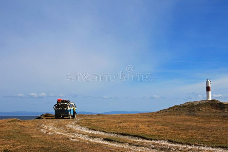 Old german vintage campervan camping at the lighthouse and the bay of Porvernir, Chile royalty free stock image