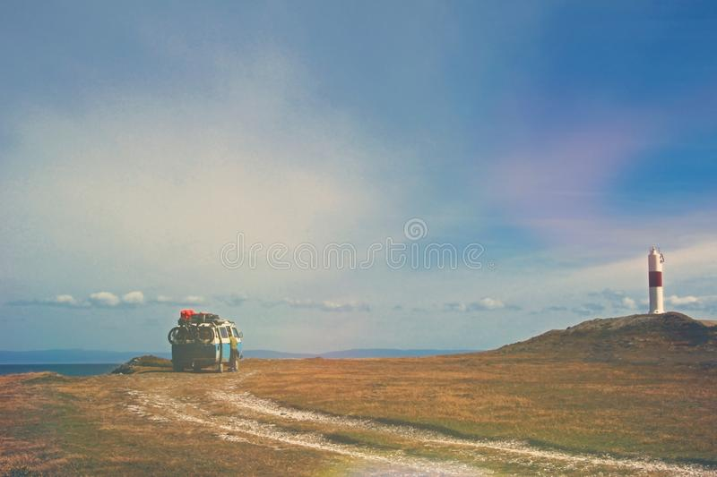 Old german vintage campervan camping at the lighthouse and the bay of Porvernir, retro vintage photo filter effect in stock photography