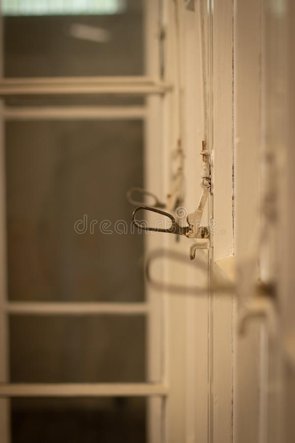 Old glass wall with doors, focus on window handle stock images