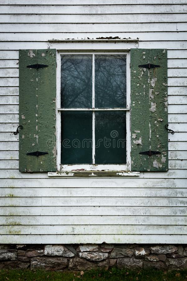 Old Glass Windows. An old glass window is surround by peeling paint and in need of repair royalty free stock images